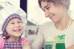 Den gulliga flickan med hennes moder bakar kakor hemma royaltyfria bilder