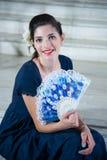 Den gulliga flickan, med långa blått klär, med fanen som sitter på bakgrundsmoment royaltyfria foton