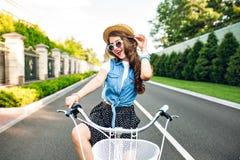 Den gulliga flickan med långt lockigt hår i solglasögon passerar cykeln till kameran på vägen Hon bär den långa kjolen, ärmlös ja royaltyfri bild