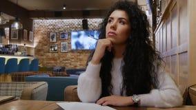 Den gulliga flickan med lockigt hår startar att skriva en dikt i en restaurang stock video