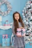 Den gulliga flickan nära julgranen tycker om mirakelvintertid Julfilial och klockor Tro i mirakel royaltyfri bild