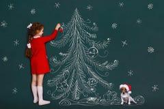 Den gulliga flickan och hennes stålarrussell hund med dekorerar jul tr Arkivbilder