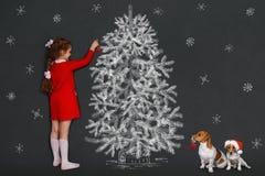 Den gulliga flickan och hennes stålarrussell hund med dekorerar jul tr Royaltyfria Bilder