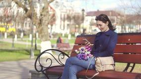 Den gulliga flickan parkerar på våren tycker om le för telefon stock video