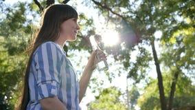 Den gulliga flickan rymmer glasflaskan in i handen och dricker kallt rent vatten parkerar in på bakgrundsträd i panelljus stock video