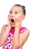Den gulliga flickan rymmer hennes framsida i häpnad Royaltyfria Bilder
