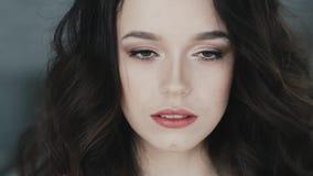 Den gulliga flickan ser försiktigt in i kamerakameran Stående av en ung brunett långsam rörelse stock video