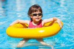 Den gulliga flickan simmar i en pöl i en gul livpreserver Royaltyfri Foto