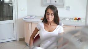 Den gulliga flickan sitter ner, i tandläkarestol och att le på kameran stock video
