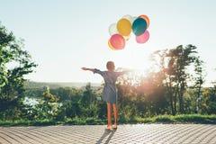 Den gulliga flickan som rymmer färgrika ballonger i staden, parkerar spreding ar Arkivbilder