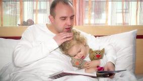 Den gulliga flickan som sovande faller, medan älska fadern, läste boken med sagor i säng arkivfilmer