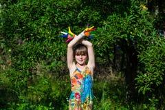 Den gulliga flickan som visar hennes händer, målade i ljusa färger händer målad gå white Arkivfoton