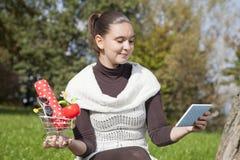 Den gulliga flickan tänker shoppar omkring online Arkivbild