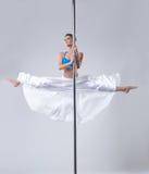 Den gulliga flickan utför lätt gymnastisk splittring på pol Arkivfoton