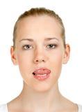 den gulliga flickan visar tungan Arkivfoton