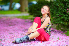 Den gulliga flickarulle-skateboradåkaren i vår parkerar Arkivbilder