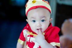 Den gulliga fokusen behandla som ett barn den röda och guld- kinesiska dräkten för pojkekläder på kinesisk dag för nytt år Royaltyfria Bilder