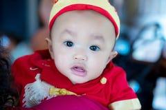 Den gulliga fokusen behandla som ett barn den röda och guld- kinesiska dräkten för pojkekläder på kinesisk dag för nytt år Royaltyfria Foton