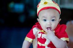 Den gulliga fokusen behandla som ett barn den röda och guld- kinesiska dräkten för pojkekläder på kinesisk dag för nytt år Arkivfoto