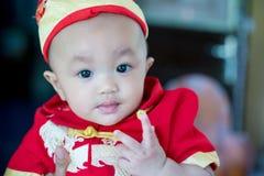 Den gulliga fokusen behandla som ett barn den röda och guld- kinesiska dräkten för pojkekläder på kinesisk dag för nytt år Arkivbilder