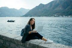 Den gulliga freelancerkvinnan i grå kofta och blåttryggsäck skriver Royaltyfria Bilder