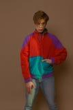 Den gulliga grabben i hipster beklär 90-tal som poserar i studio Royaltyfri Foto