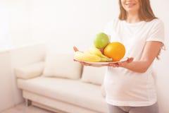 Den gulliga gravida kvinnan är att att bry sig av hennes hälsa arkivbilder