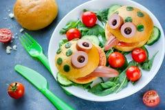 Den gulliga grodan formade hamburgaren på en platta med nya grönsaker Fotografering för Bildbyråer