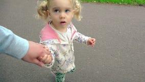 Den gulliga handen för liten flickainnehavfadern och går tillsammans stock video