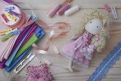 Den gulliga handgjorda dockan på en trätabell med färgrika tyger som stickas snör åt, pastellfärgade band och symöblemang arkivfoto