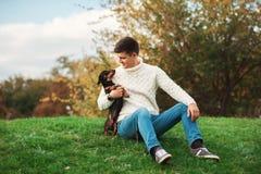 Den gulliga hunden och hans unga stiliga man för ägare har gyckel i parkera, befruktningdjur, husdjur, kamratskap arkivbild