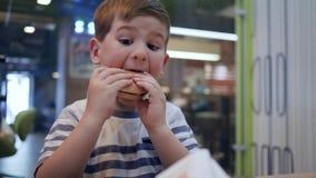 Den gulliga hungriga pojken släcker hunger med skadligt mål i gatakafét, pysåt på tabellhamburgaren med en aptit arkivfilmer
