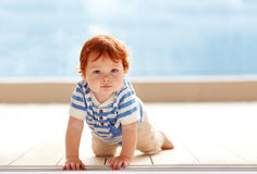 Den gulliga ingefäran behandla som ett barn pojkekrypning på golvet Royaltyfri Foto