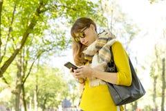 Den gulliga kvinnan är det läs- angenäma textmeddelandet på mobiltelefonen, medan ta en gå i parkera i varm nedgångdag royaltyfri foto