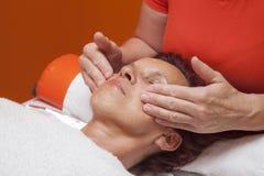 Den gulliga kvinnan får den yrkesmässiga ansikts- massagen, lymfatisk dränering Arkivfoton