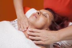 Den gulliga kvinnan får den yrkesmässiga ansikts- massagen, lymfatisk dränering Royaltyfria Foton