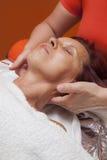 Den gulliga kvinnan får den yrkesmässiga ansikts- massagen, lymfatisk dränering Arkivbild