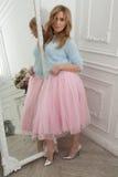 Den gulliga kvinnan i rosa färger kringgår och försilvrar skor i klassisk inre Royaltyfria Bilder
