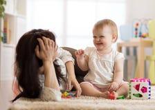 Den gulliga kvinnan och ungen spelar tillsammans inomhus royaltyfria foton
