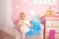 Den gulliga kvinnan ser som en docka i en söt inre Ungt nätt s Arkivfoto