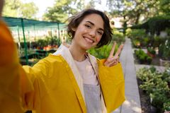 Den gulliga kvinnaträdgårdsmästaren som står över blommaväxter i växthus, gör selfie vid kameran med fred att göra en gest royaltyfri foto