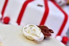 Den gulliga läckra bröllopstårtan dekorerade med kakor i formen av röda och vita rosor Royaltyfri Bild