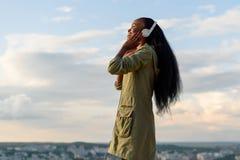 Den gulliga le afrikansk amerikanflickan lyssnar musik och att koppla av Suddig cityscapebakgrund utomhus- stående Arkivfoton