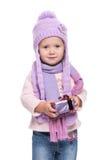 Den gulliga le bärande violeten för lilla flickan stack halsduken och hatten, den hållande julgåvan som isolerades på vit bakgrun Royaltyfri Foto