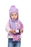 Den gulliga le bärande violeten för lilla flickan stack halsduken och hatten, den hållande julgåvan som isolerades på vit bakgrun Royaltyfri Bild