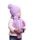 Den gulliga le bärande violeten för lilla flickan stack halsduken och hatten, den hållande julgåvan som isolerades på vit bakgrun Fotografering för Bildbyråer
