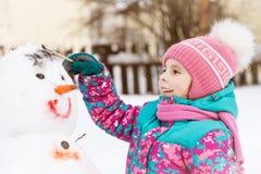 Den gulliga le flickan målar en snögubbe Royaltyfri Fotografi