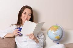 Den gulliga le flickan med en blå kopp och dagboken som sitter på soffan i rummet och, läser Fotografering för Bildbyråer