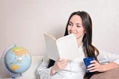 Den gulliga le flickan med en blå kopp och dagboken som sitter på soffan i rummet och, läser Royaltyfria Foton