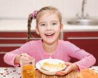 Den gulliga le lilla flickan som har frukostsädesslag med, mjölkar royaltyfri bild